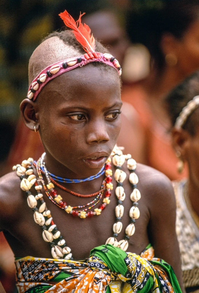 Young Voodoo Priestess with Red Parrot Feather, Benin